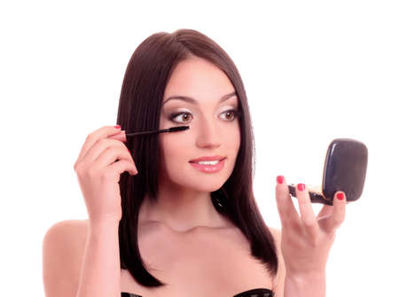 Beautiful young woman with mascara brush and hand mirror Stock Photo - 9579487