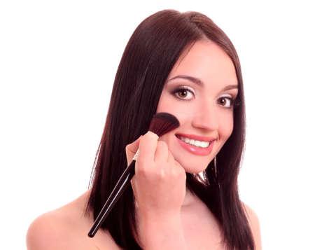 Beautiful young woman applying blusher photo