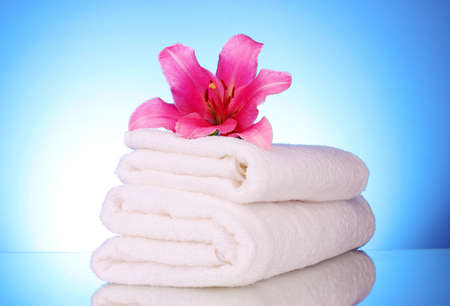 downy: stack of towels with pink lily  on blue background