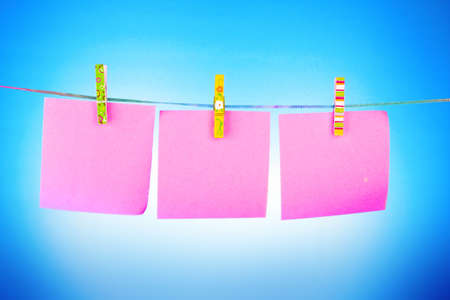 Blank paper sheets on a clothes line on a blue background photo