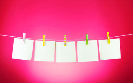 Blank paper sheets on a clothes line against the pink background Stock Photo - 9579374