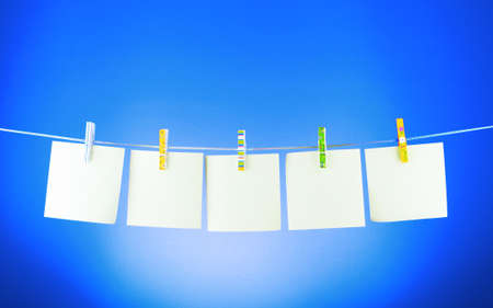 laundry line: Blank paper sheets on a clothes line on a blue background