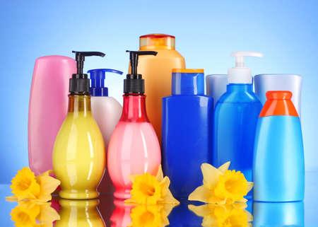 botellas de productos de salud y belleza sobre fondo azul con reflexión