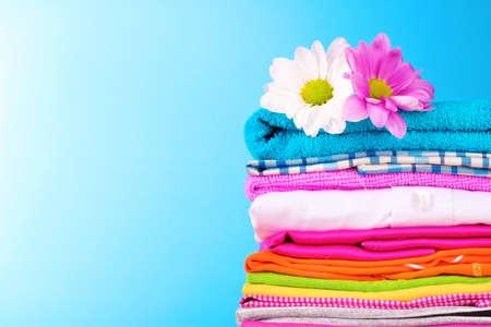 ropa casual: Pila de ropa color y flores sobre fondo azul