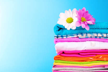 Pile of colorful clothes and flowers   on blue background Stock fotó