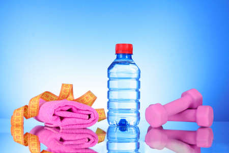 dumbbells and bottle of fresh water on blue Stock Photo - 9633333