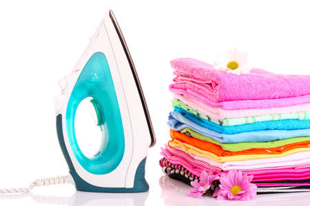 Pile of colorful clothes and electric iron  over white background Stock Photo - 9683642