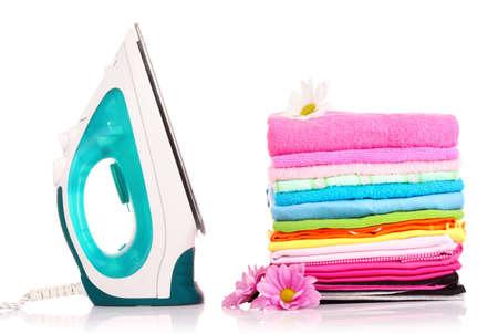 ropa casual: Pila de ropa colorida y plancha el�ctrica sobre fondo blanco