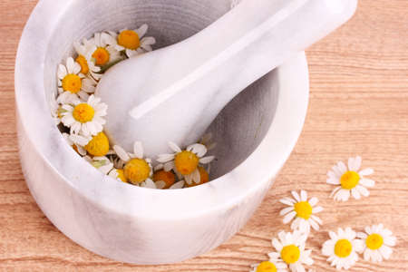 chamomile flowers in a mortar on brown photo