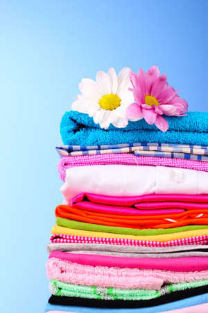 Pile of colorful clothes and flowers   on blue background photo