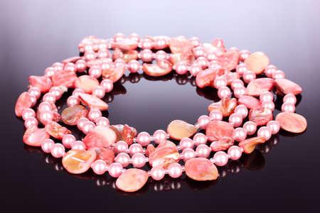 perle rose: roses colliers de perles et de coquillages sur un fond gris