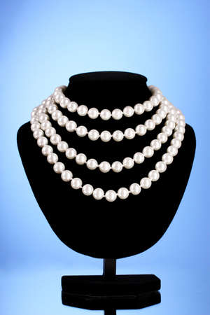 a pearl necklace on a blue background photo
