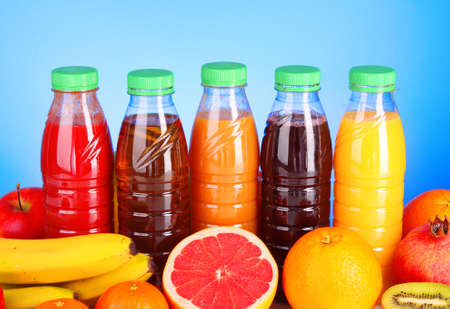 bottles of juice  with ripe fruits on blue background photo