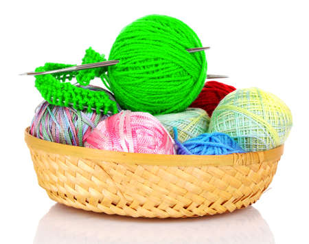 Balls of color knitting wool or yarn in basket on white photo