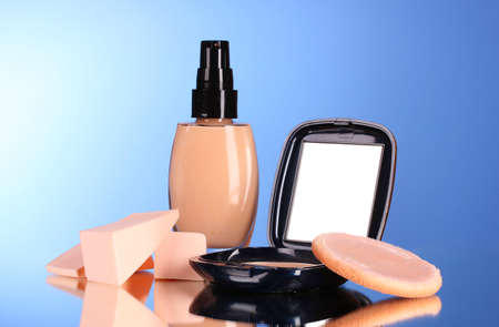 concealer: concealer, face powder and sponges on a blue background Stock Photo