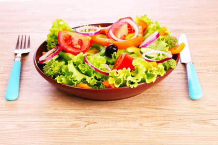many vegetables on the plate on a wooden background photo
