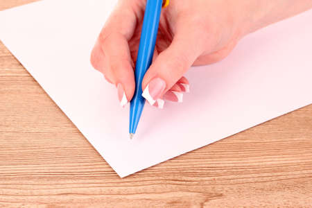 Womens hand, a pen and paper on wooden background photo