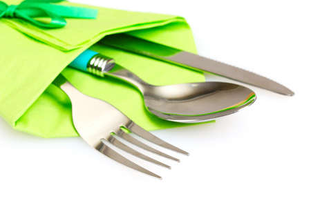knife, fork and spoon in green cloth, isolated on white photo