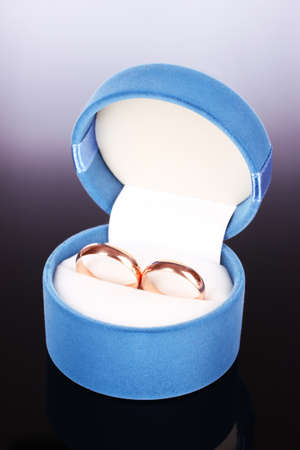 wedding rings in the blue box on black background photo