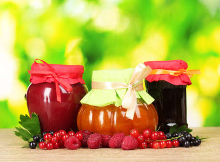 tasty berry and fruit jam and berry on a green background photo