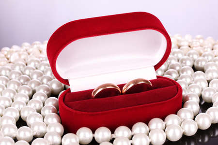 wedding rings in a box and pearls photo
