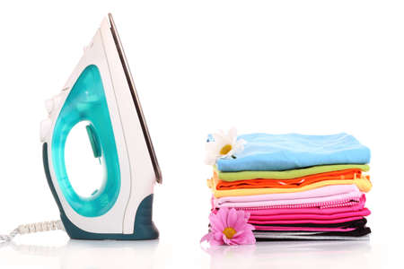 Pile of colorful clothes and electric iron  over white background photo