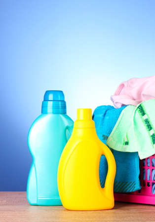 Colorful towels and liquid laundry detergent   over blue photo