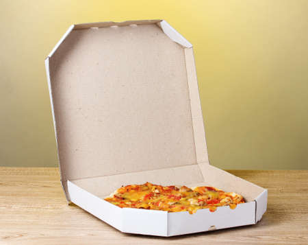 delicious pizza in package on yellow background photo