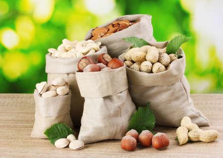 cacahuate: muchos frutos secos en bolsas sobre fondo verde