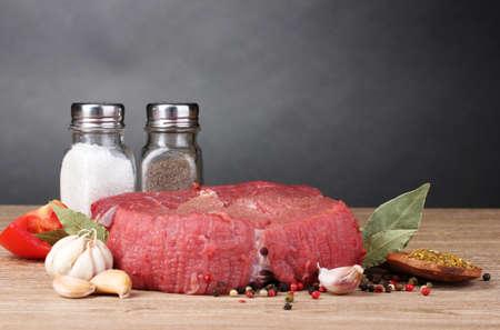 carne cruda: carne cruda, verduras y especias sobre fondo gris Foto de archivo