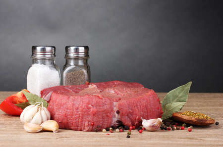 raw meat, vegetables and spices on gray background photo