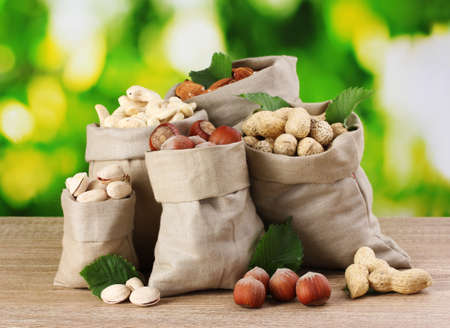 mixed nuts: variety of nuts in bags on green background