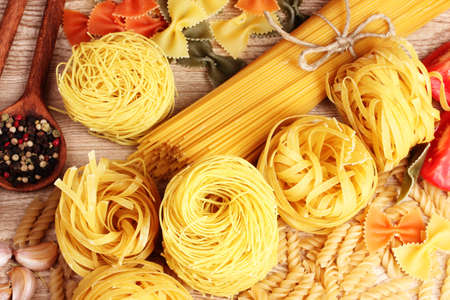 tasty vermicelli, spaghetti and spices on wooden background photo