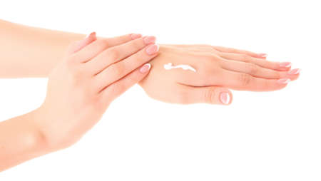 Closeup of beautiful female hands applying hand cream  on white background photo