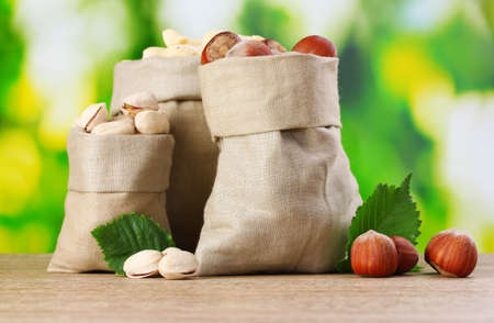 many nuts in bags on green background photo