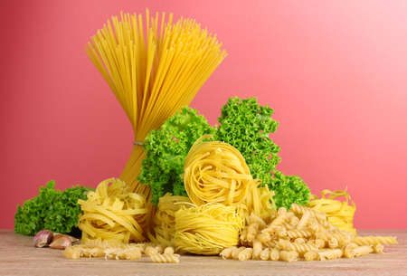 vermicelli, lettuce and oil on red background photo