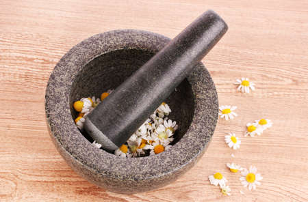 chamomile flowers in a mortar on brawn Stock Photo - 10321078