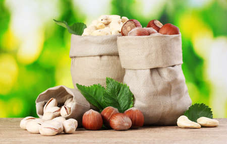 many nuts in bags on green background Stock Photo - 10321063