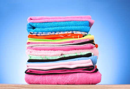 Pile of colorful clothes over blue background photo
