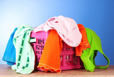 Bright clothes in a laundry basket on blue background photo