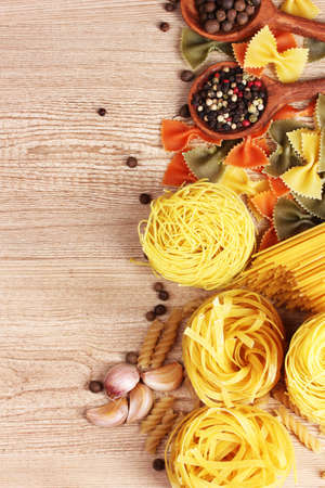 different pasta and spices on wooden background photo