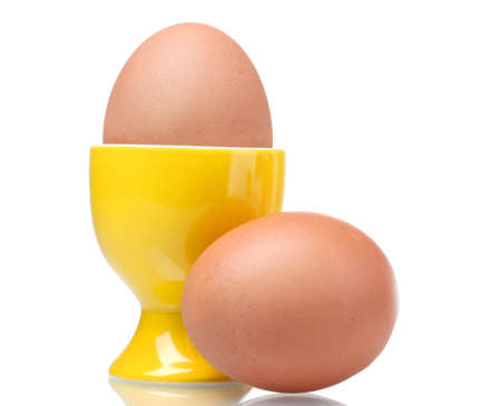 eggcup: boiled eggs in yellow stand isolated on white