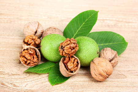 walnuts and leaves on wooden background photo