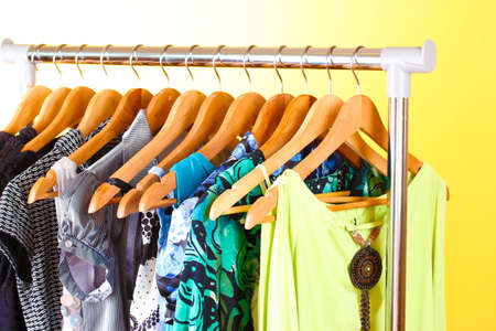 different clothes on wooden hangers on yellow background photo
