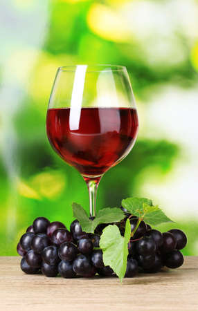 Ripe grapes and  glass of wine on  green background Stock Photo - 10438007