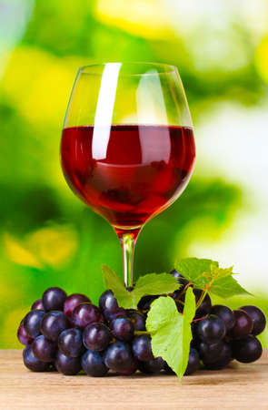 Ripe grapes and  glass of wine on  green background Stock Photo - 10460832