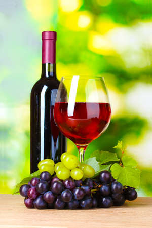 Ripe grapes, bottle and  glass of wine on  green background Stock Photo - 10487644
