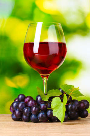 Ripe grapes and  glass of wine on  green background Stock Photo - 10487643