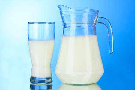milk milk products: Sabrosa leche en jarra y vidrio sobre fondo azul