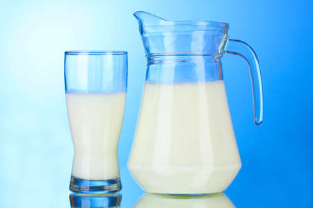 jugs: Tasty milk in jug and glass on blue background